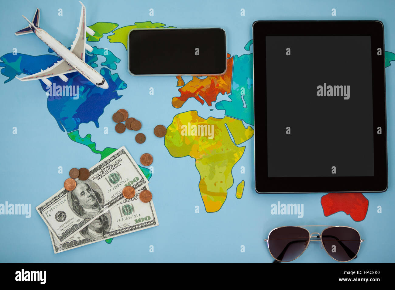Electronic gadgets, sunglasses, dollar and airplane model - Stock Image