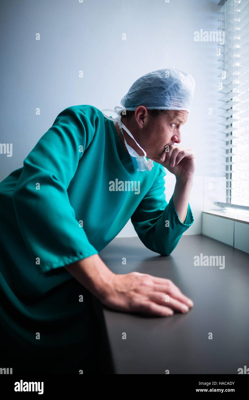 Thoughtful male surgeon looking through window - Stock Image
