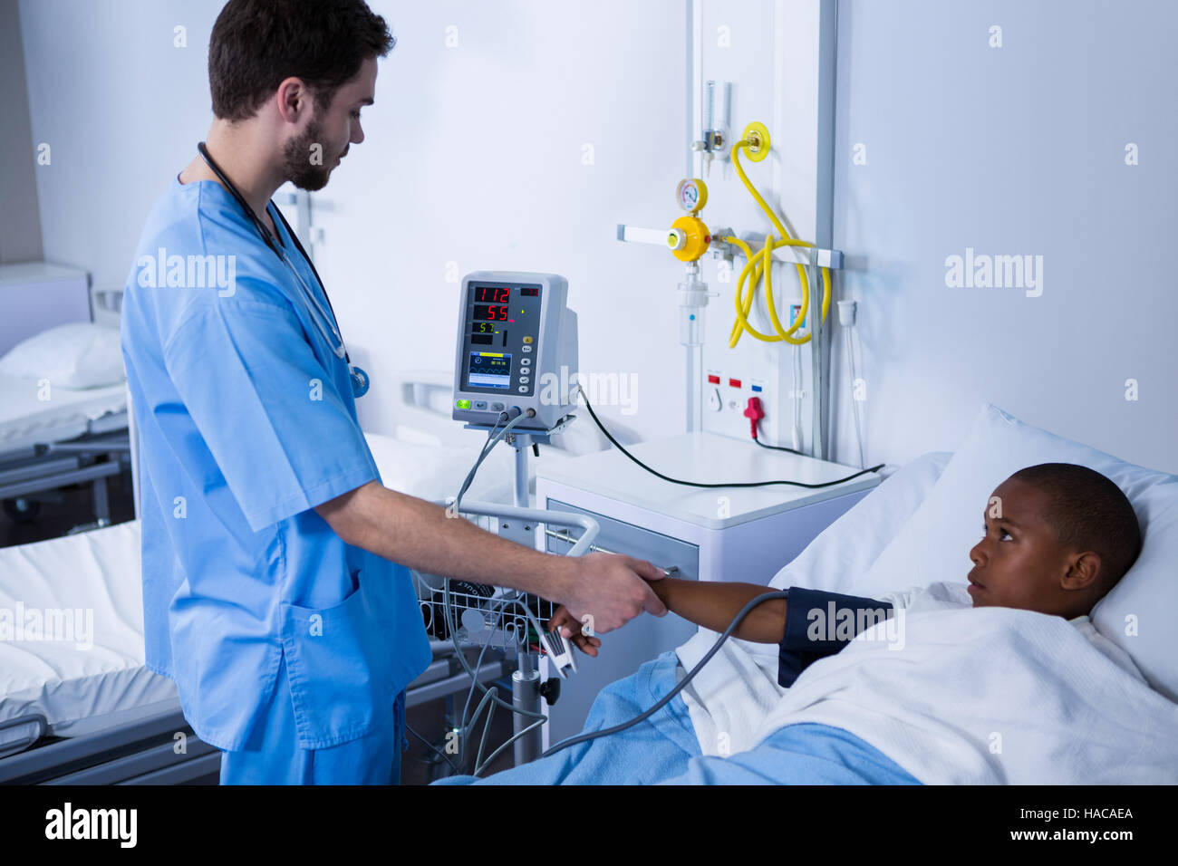 Male nurse checking patient blood pressure in ward - Stock Image