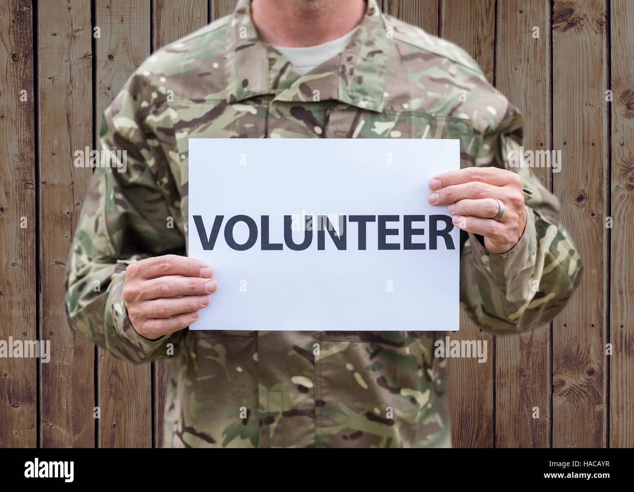 Person in camouflage uniform holding placard which reads volunteer - Stock Image