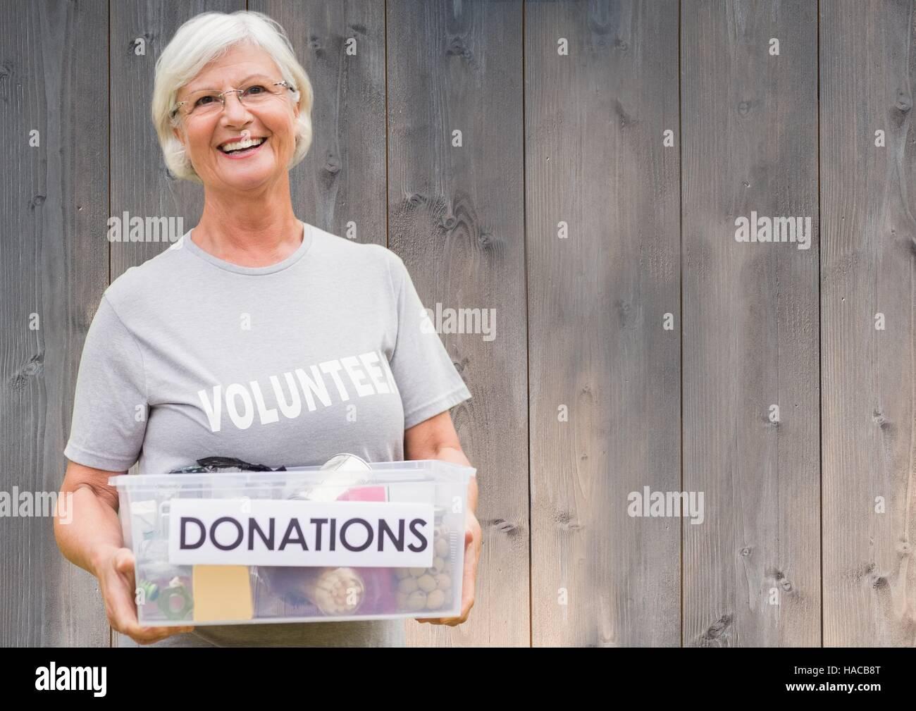 Smiling female volunteer holding donations box - Stock Image