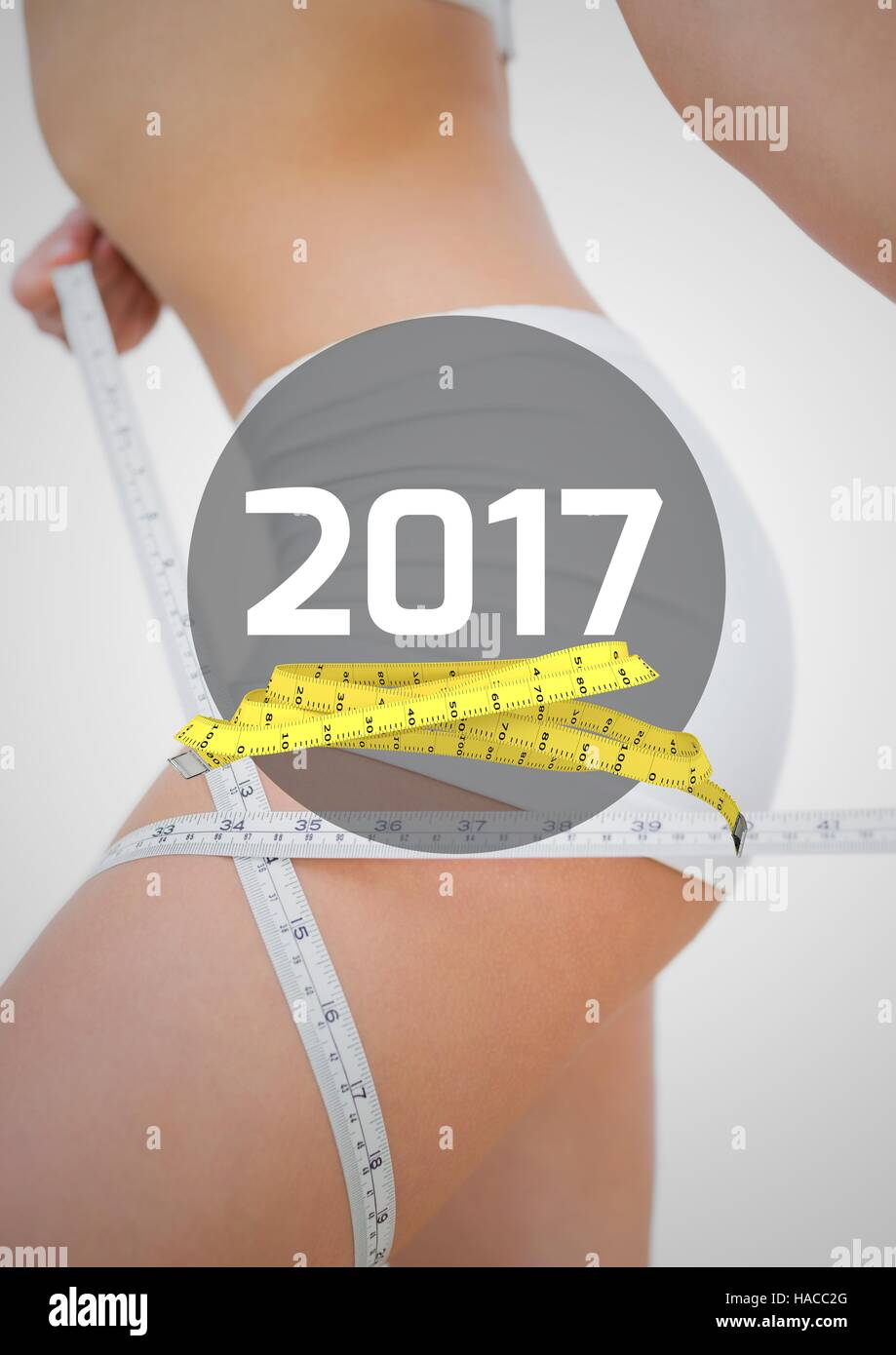 Woman measuring her thigh against 2017 - Stock Image