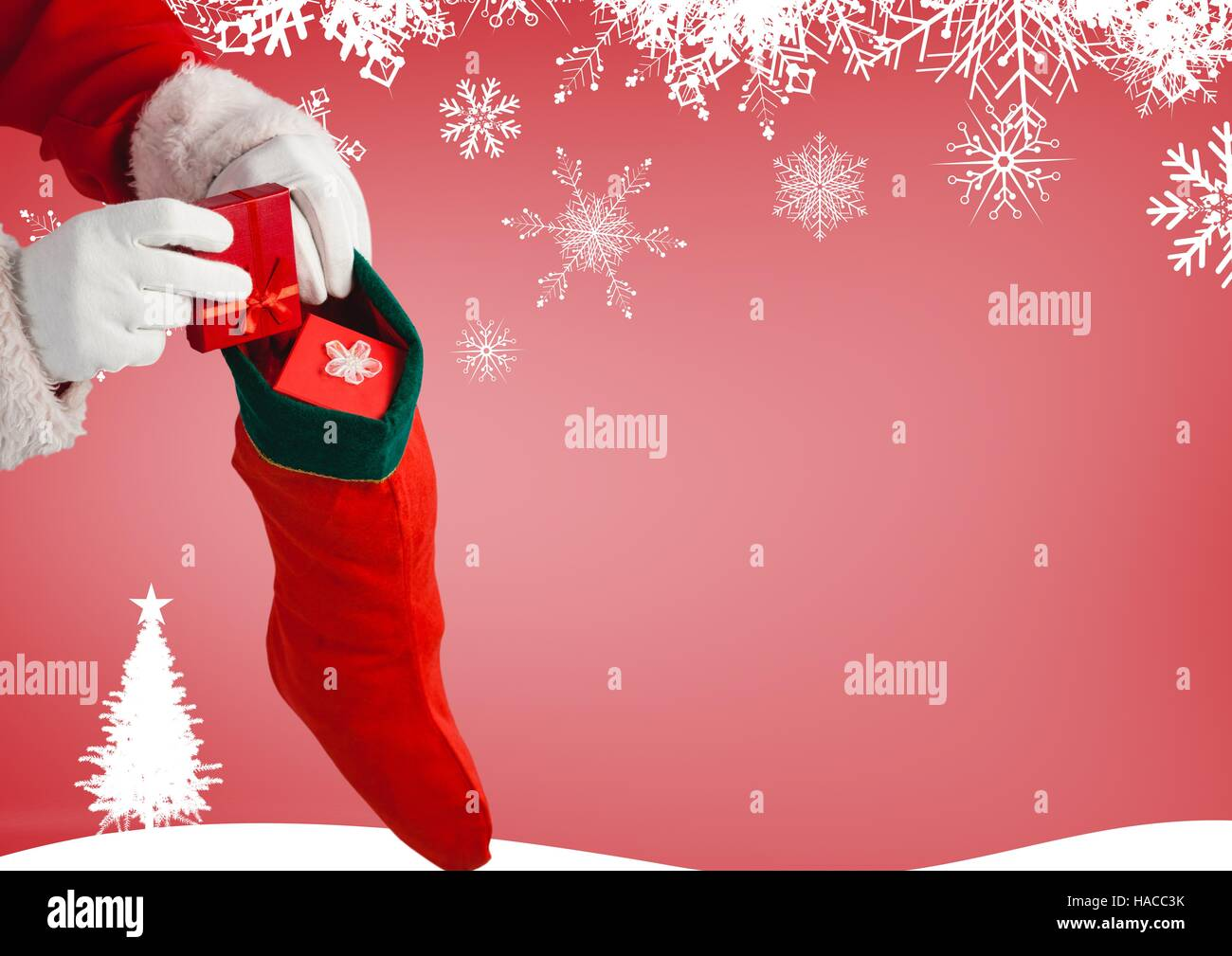 Santa claus putting gifts in christmas stockings Stock Photo