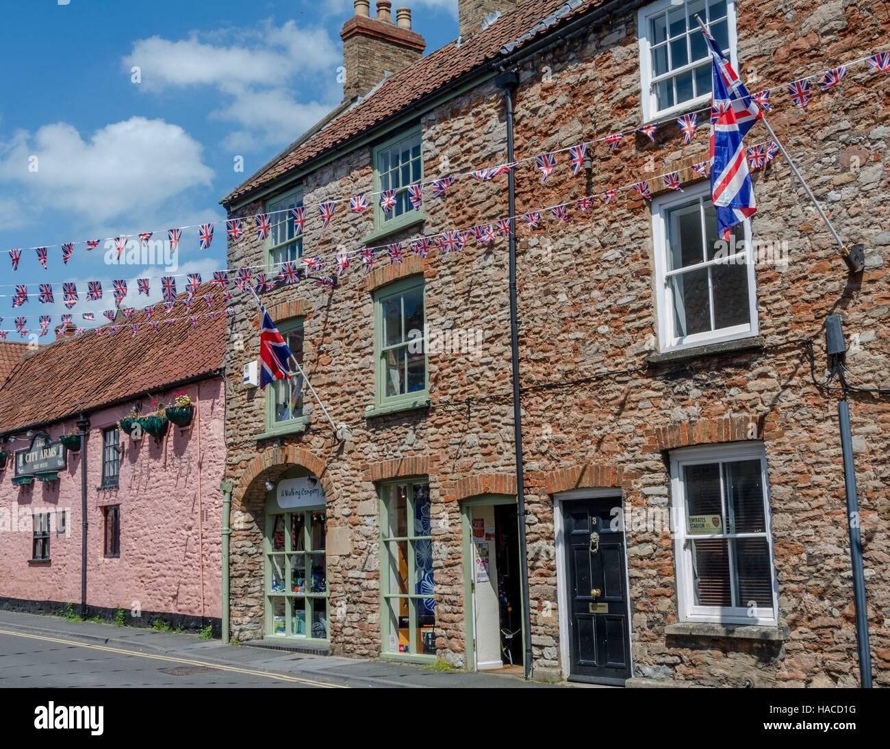 UK flags fly in the street outside the City Arms pub in Glastonbury, England - Stock Image