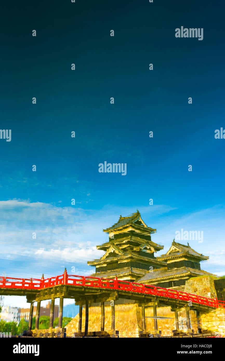 A painterly mirror image of Matsumoto Castle upside down seen as water reflection on a blue sky day in Nagano Prefecture, - Stock Image