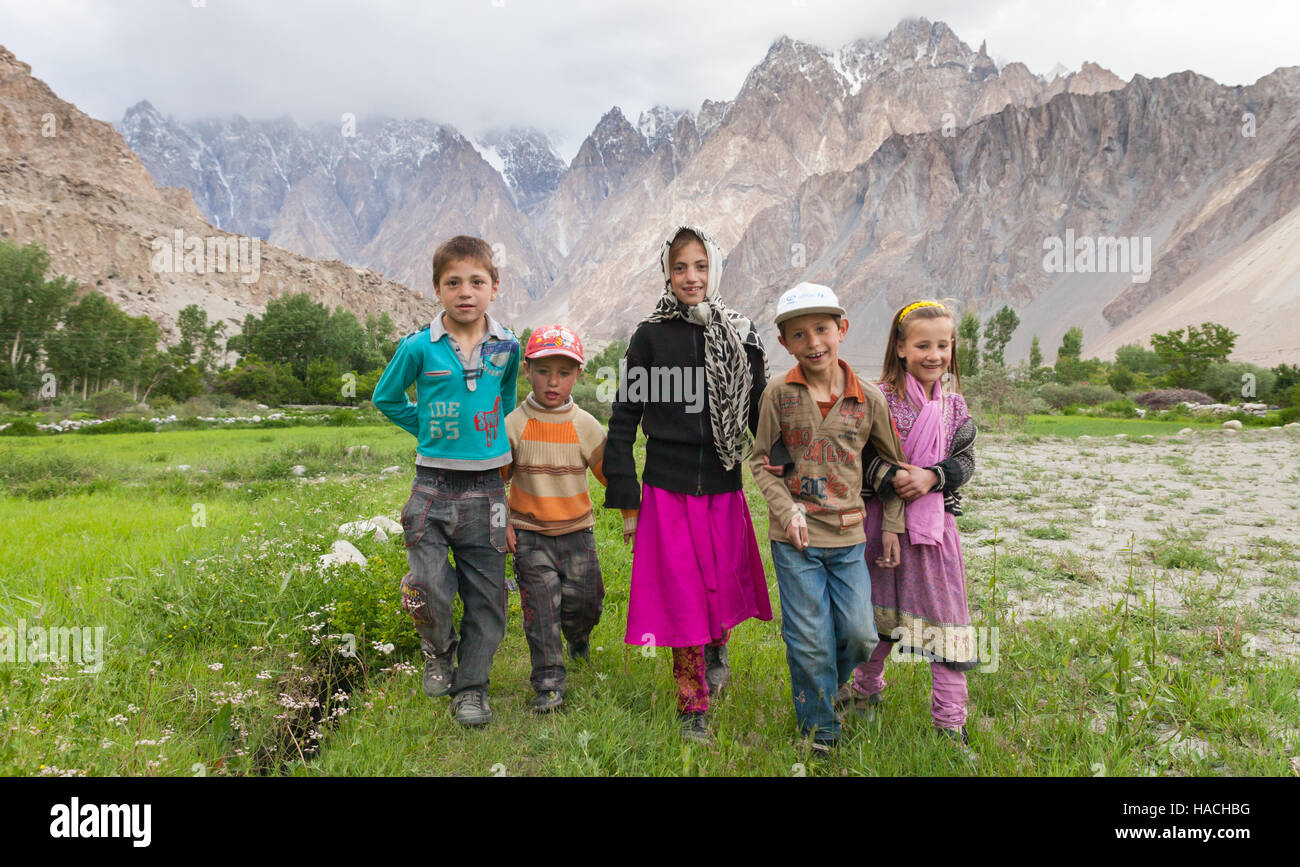 Pakistani children taking a walk on meadow with magnificent Tupopdan peaks for background in Passu, northern Pakistan - Stock Image