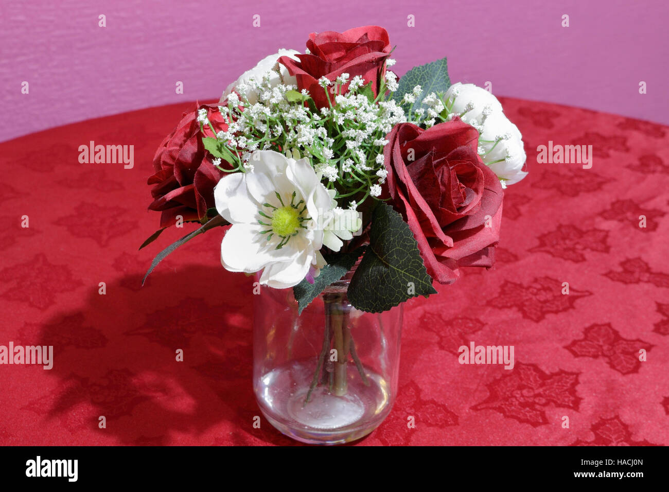 Decorative Plastic Flowers In A Glass Jar With Red Table Cloth