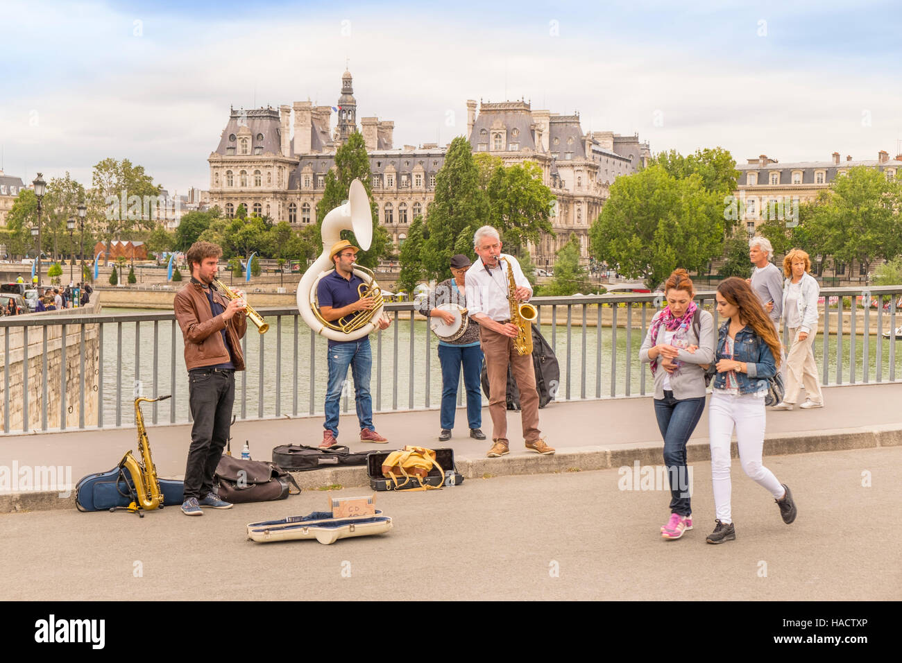 street musicians and tourists on pont saint-louis bridge, town hall (hotel de ville) in the background - Stock Image