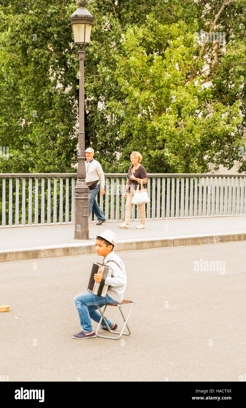 roma child street musician buskin on pont saint louis - Stock Image