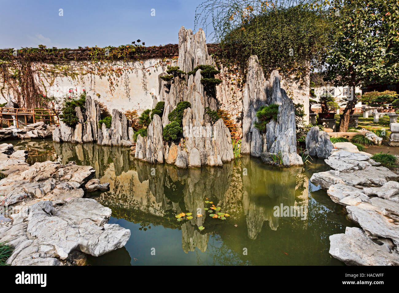 Mini rock formation from still water pond in a public garden of ...