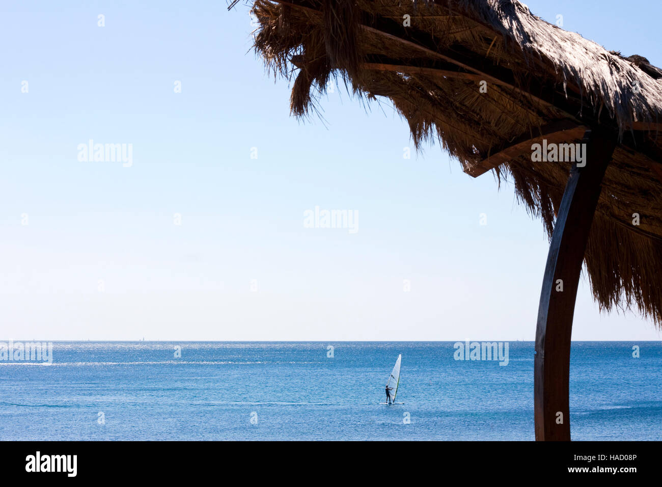 Straw umbrella on beach with wind surfer in the sea - Stock Image