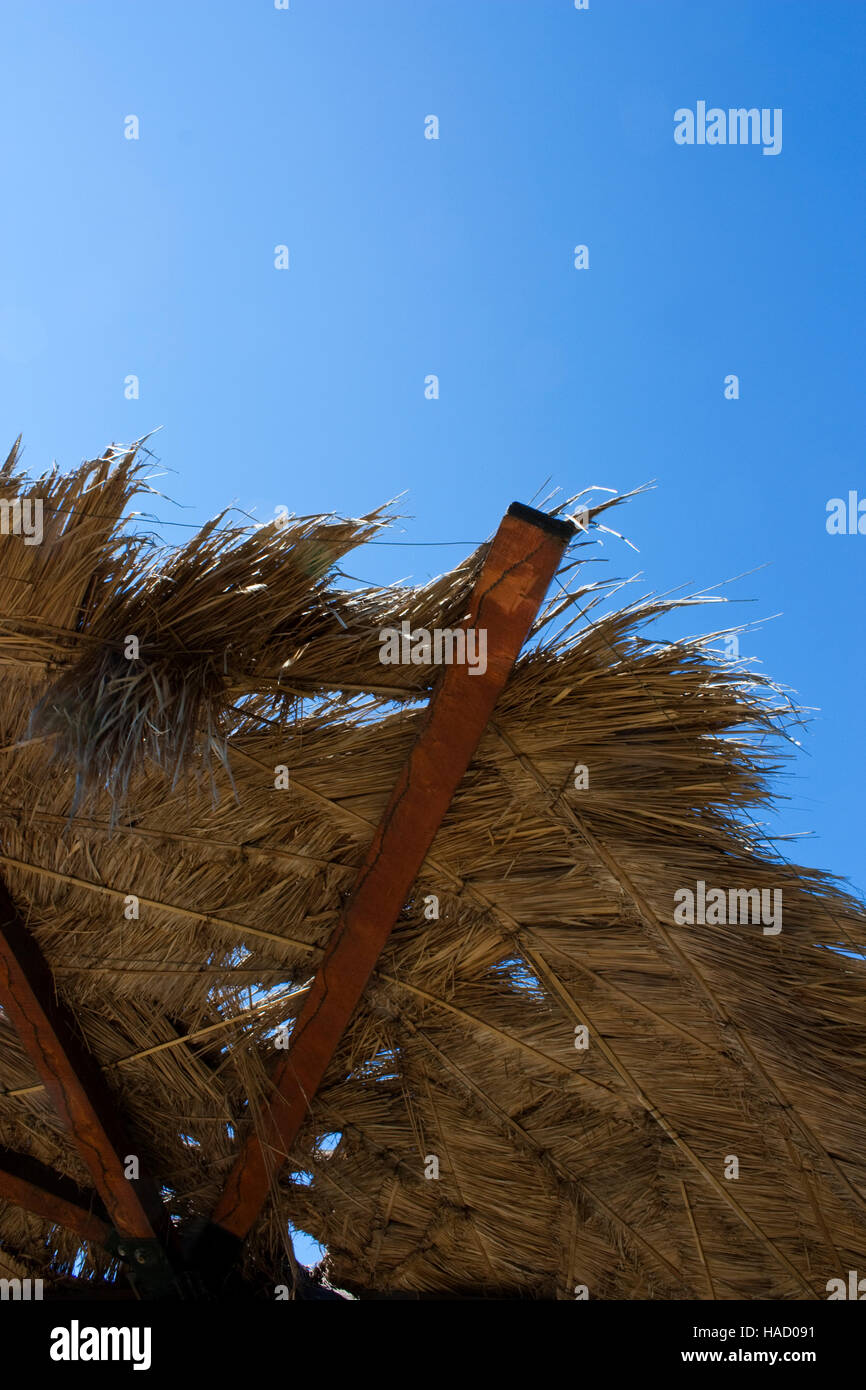straw umbrella with view to blue sky - Stock Image