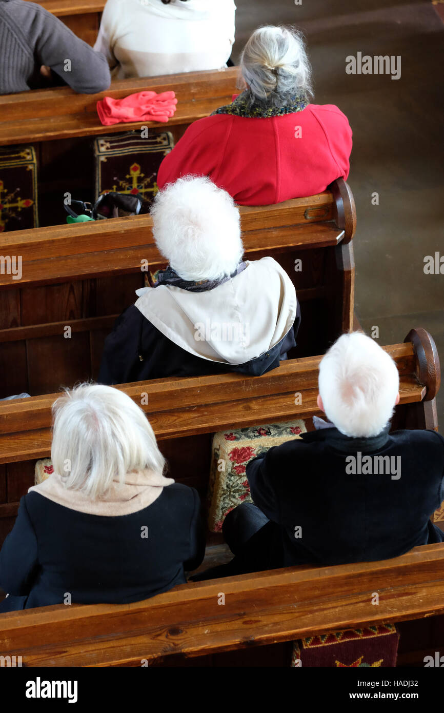 Herefordshire, UK old mature people attend a church service and sit in the congregation. - Stock Image