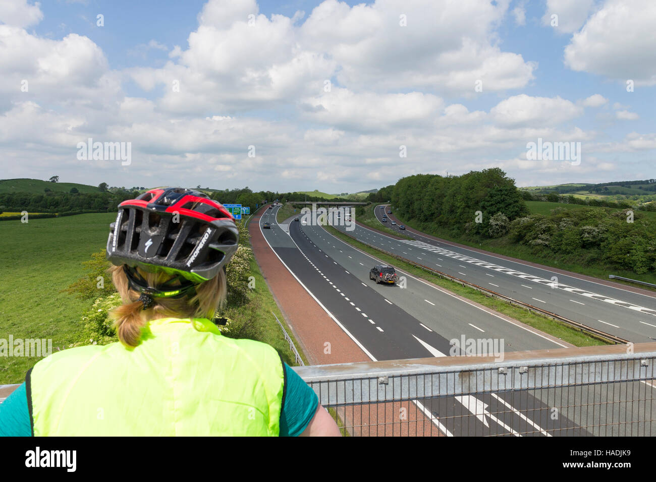 Cyclist Looking Down onto the M6 Motorway from a Section of the Lakes and Dales Loop Cycle Way in Lancashire. UK - Stock Image