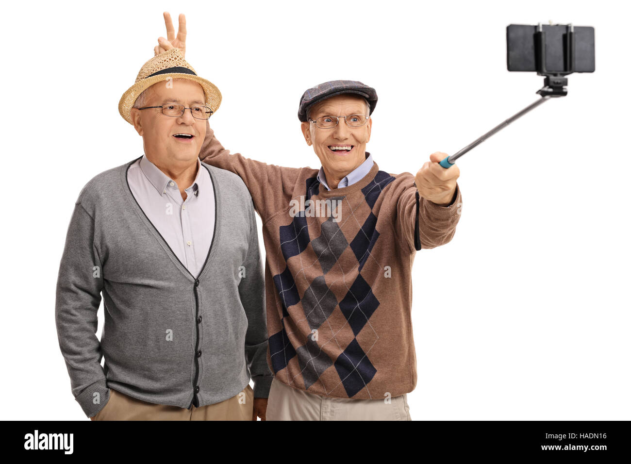 Elderly man pranking another man with bunny ears and taking a selfie with a stick isolated on white background - Stock Image