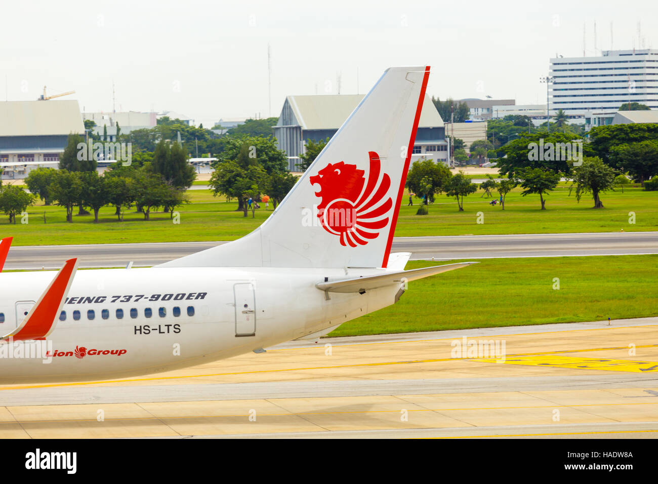 Tail section of Thai Lion Air airplane taxiing on runway at Don Mueang Airport. - Stock Image