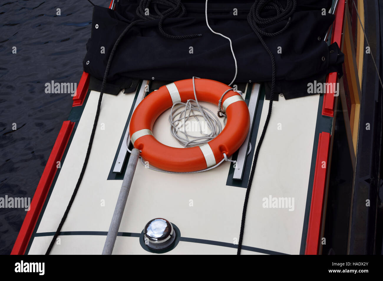 The orange life buoy ring on the boat on the Birmingham old canal - Stock Image