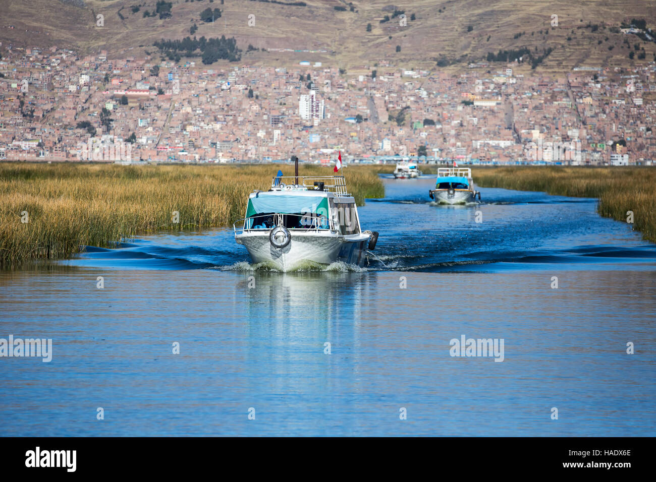 Tourist boats on Lake Titicaca flanked by totora reed fields, City of Puno in background, Puno, Peru - Stock Image