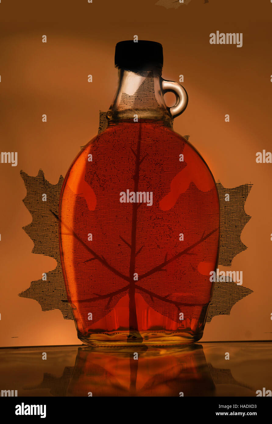 A maple leaf makes a background for a bottle of maple syrup. - Stock Image