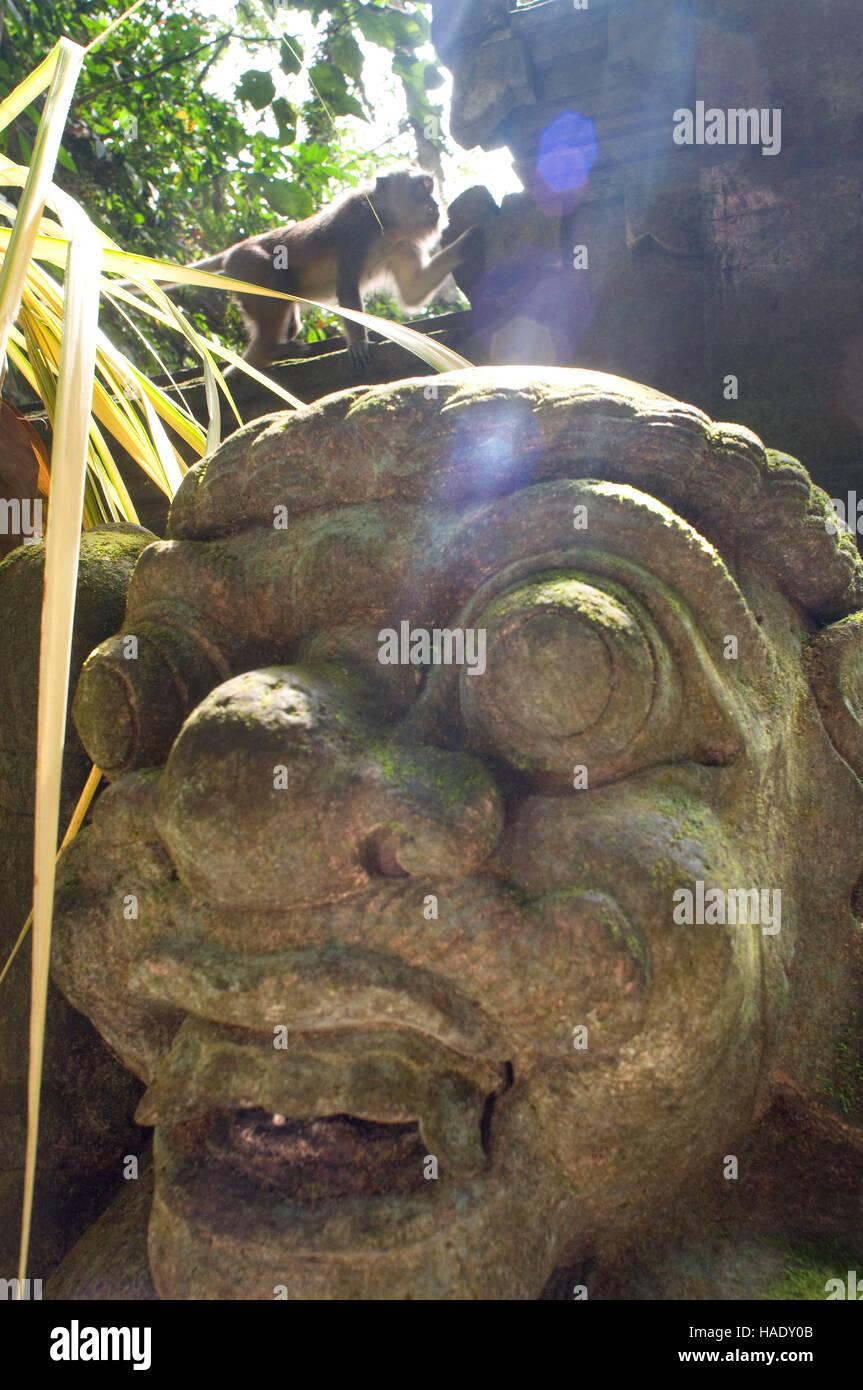Monkeys having fun on stone statues of Hindu Holy Monkey Forest. Ubud. Bali. The Ubud Monkey Forest is a nature - Stock Image