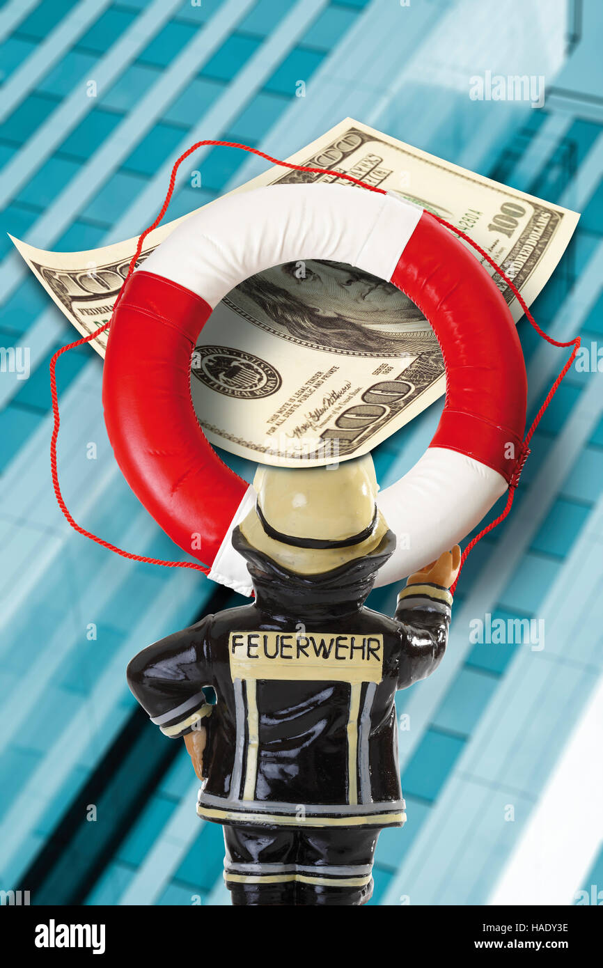 Fireman holding a lifebuoy with US dollar banknotes/greenbacks in front of a bank building, symbolic of the bank - Stock Image