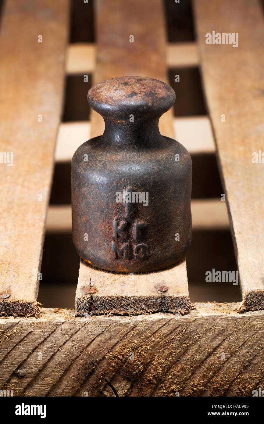 Rusty 1kg weight on the box. - Stock Image