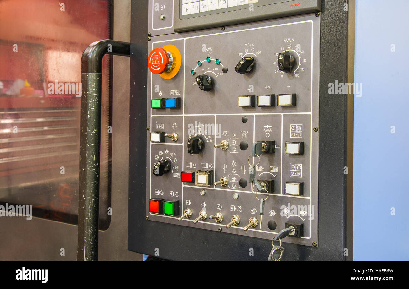 Modern CNC machining center with control panel on foreground. Close up view. Selective focus. Control panel of CNC - Stock Image