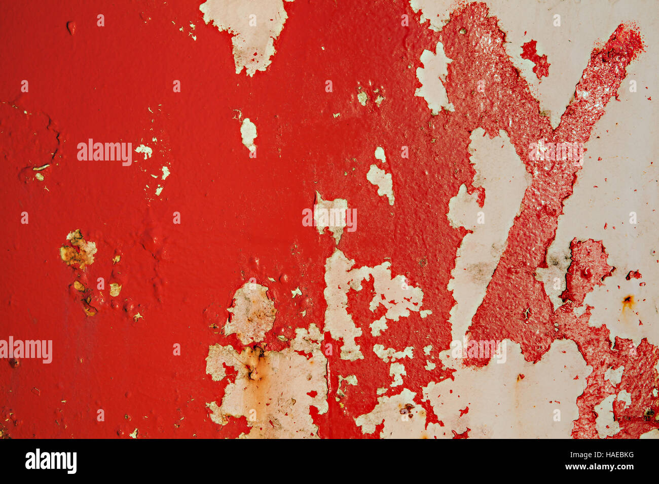 Textured red metal grunge background with peeling distressed paint rust and decay - Stock Image