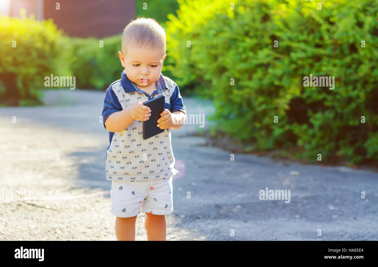 Focused little boy with a smartphone in hand. Walk in nature with sunlight. - Stock Image
