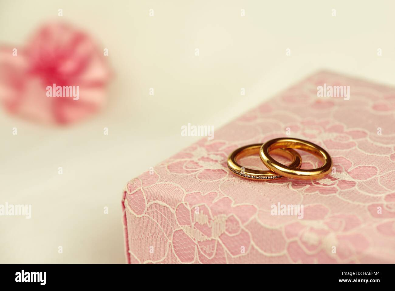 Wedding rings on a pink gift box with a ribbon flower in the background - Stock Image