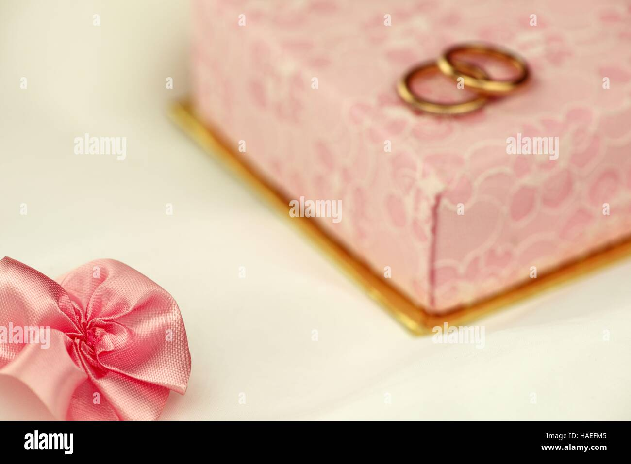 Pink ribbon bow with a gift box and wedding rings in the background - Stock Image