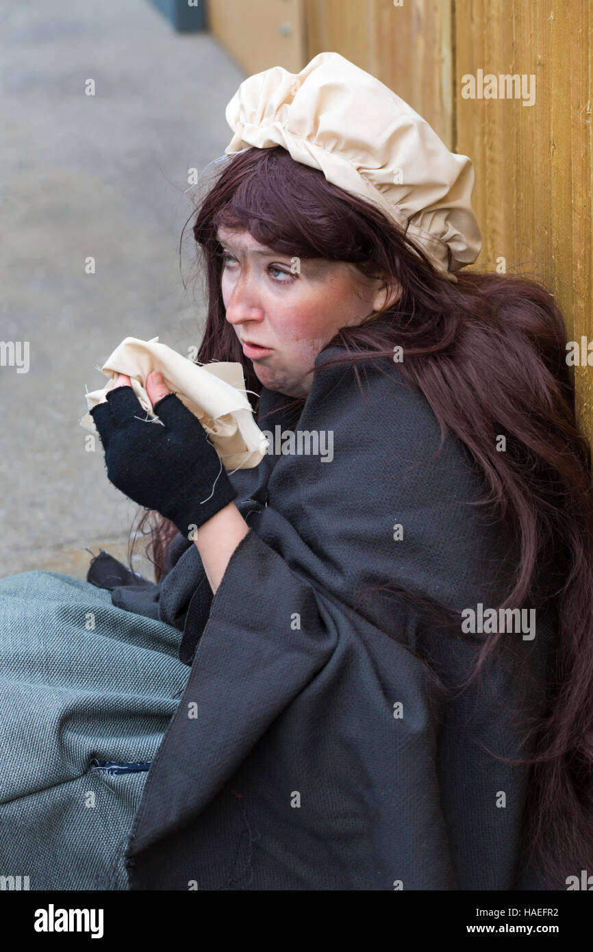 Poor girl on street offering handkerchief at Victorian Festival of Christmas at Portsmouth, Hampshire, England UK - Stock Image