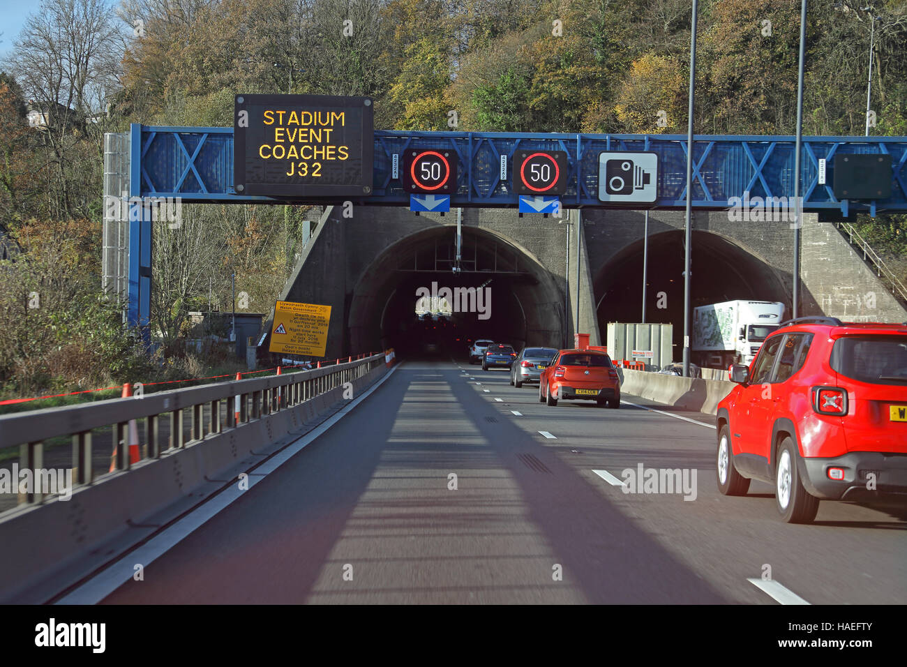 Looking towards the westerly bore of the M4 tunnel with a 50 mph restriction and other signs on a gantry over the Stock Photo