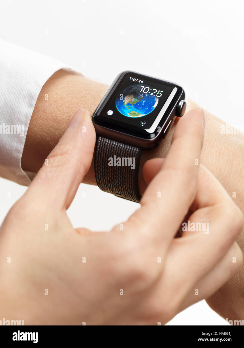 Woman hand with Apple Watch smartwatch on her wrist on white background - Stock Image