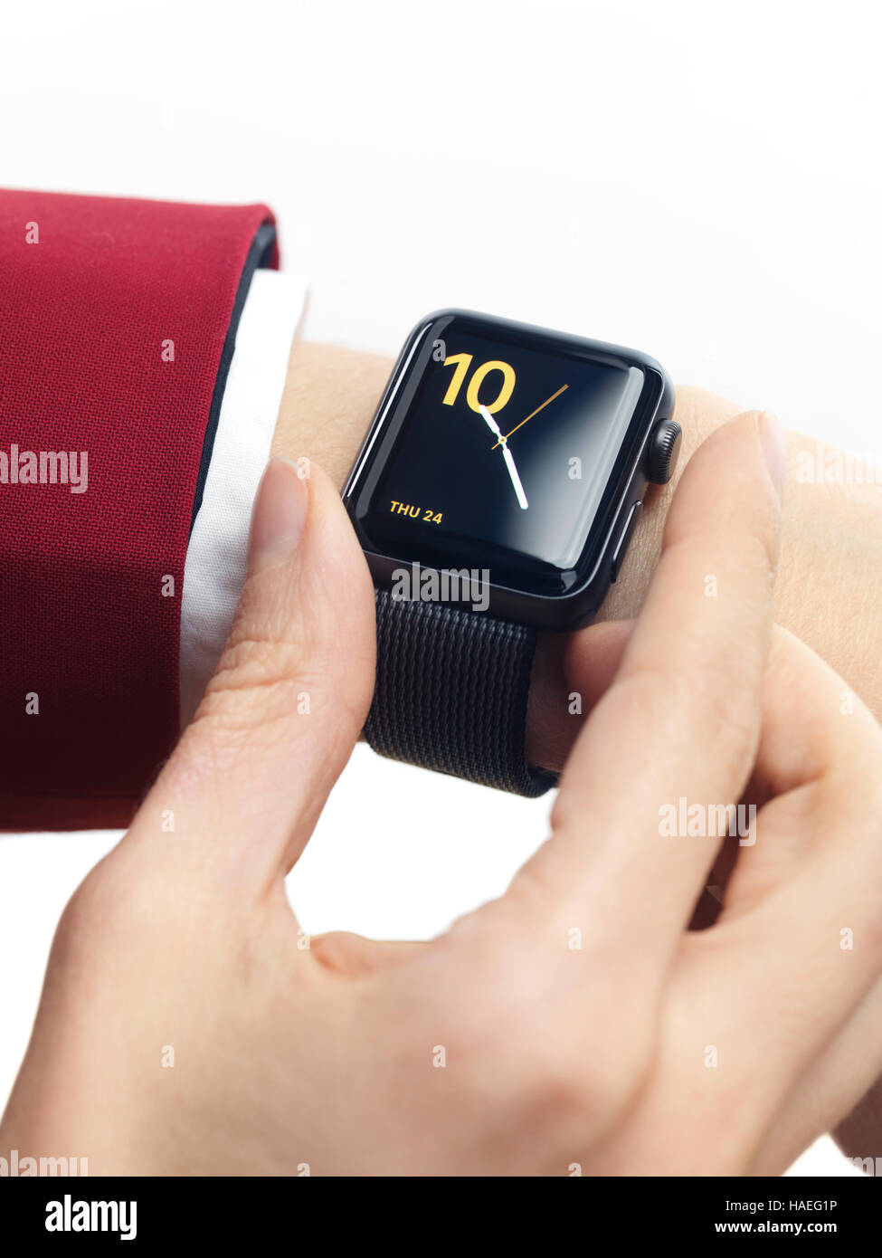 Woman hand in red suit with Apple Watch smartwatch on her wrist displaying clock isolated on white background - Stock Image