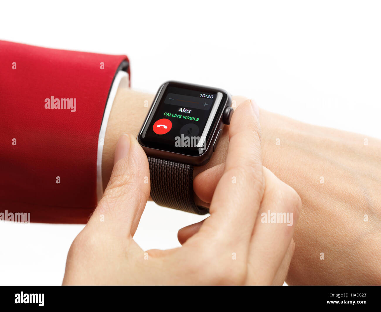Woman hand with Apple Watch smartwatch on her wrist displaying incoming phone call isolated on white background - Stock Image