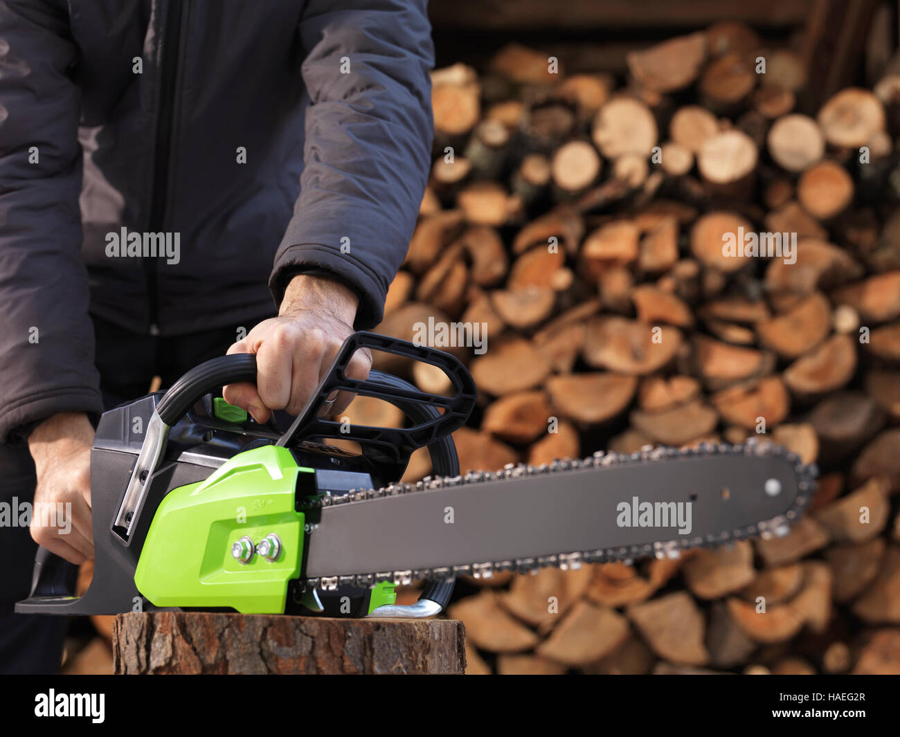 CLoseup of hands of a man holding an Electric Cordless chainsaw in front of stacked firewood in the background Stock Photo