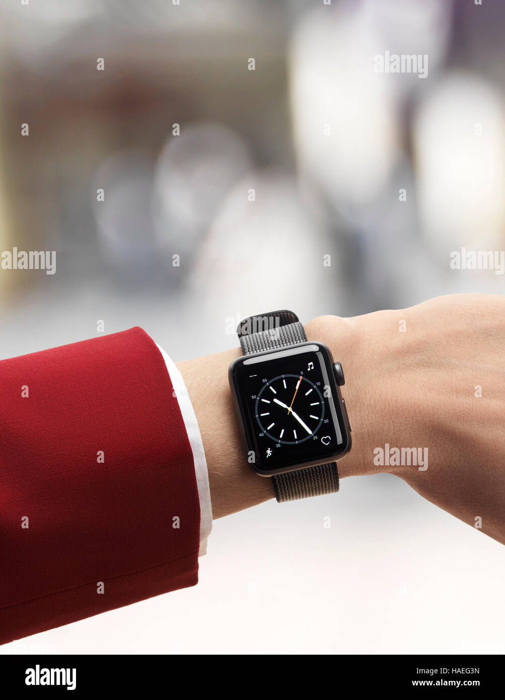 Woman hand with Apple Watch smartwatch on her wrist in outdoor urban scenery isolated on white background - Stock Image