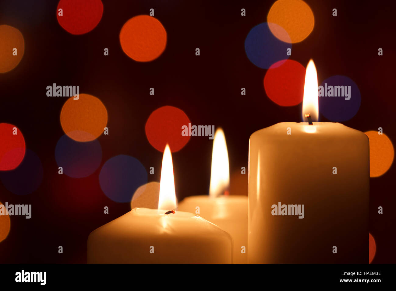 Christmas candles, with bokeh spot lights in the background - Stock Image