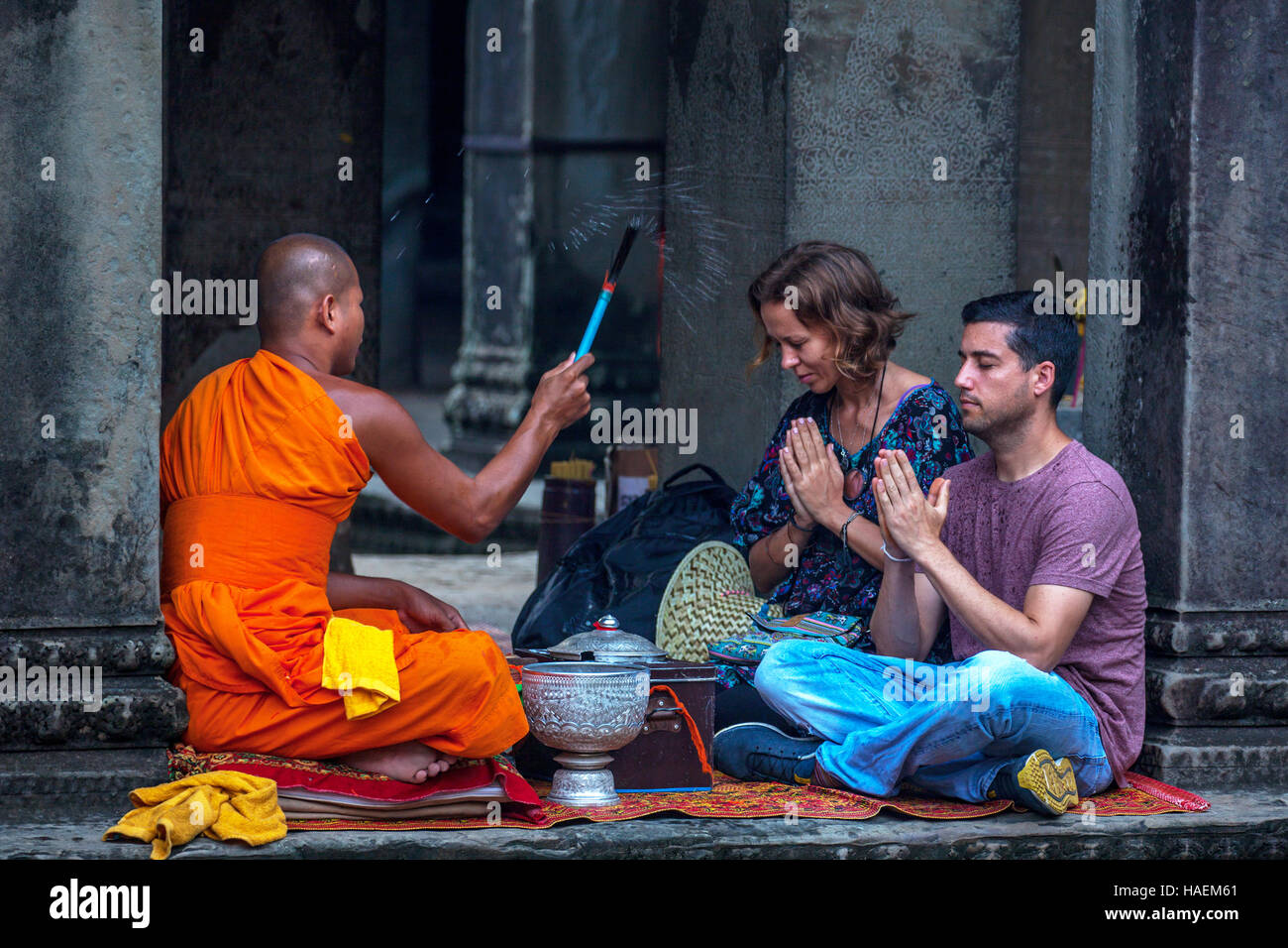 A western couple receive a blessing from a Buddhist monk at Angkor Wat in Siem Reap, Kingdom of Cambodia. Stock Photo