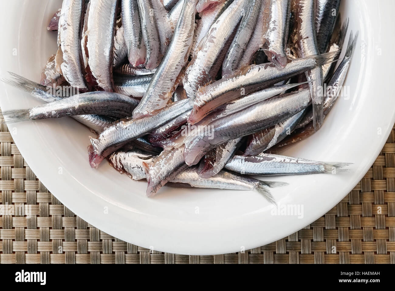 Anchovies headless, clean and ready to be cooked. white plate - Stock Image