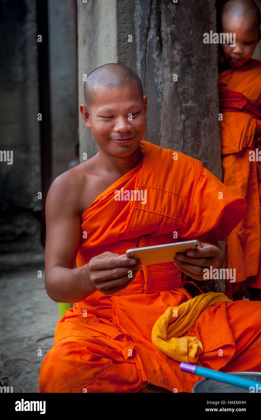 Smiling Buddhist monk in traditional orange robe looking at his smartphone in Angkor Wat temple at Siem Reap, Cambodia - Stock Image