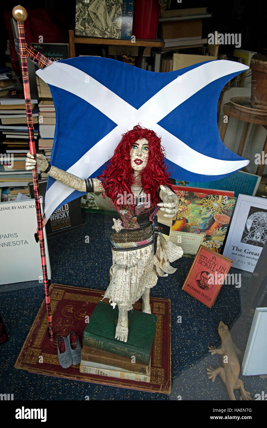 A figure made from old books showing a red-headed woman holding the Saltire in the window of a secondhand bookshop - Stock Image