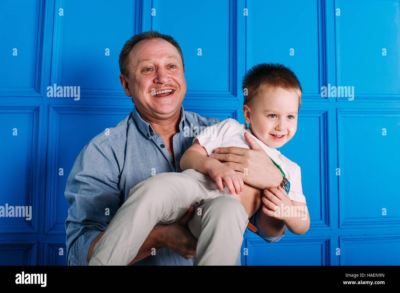 Laughing grandfather with his grandson as they play together indoors in the living room with the cute young boy - Stock Image