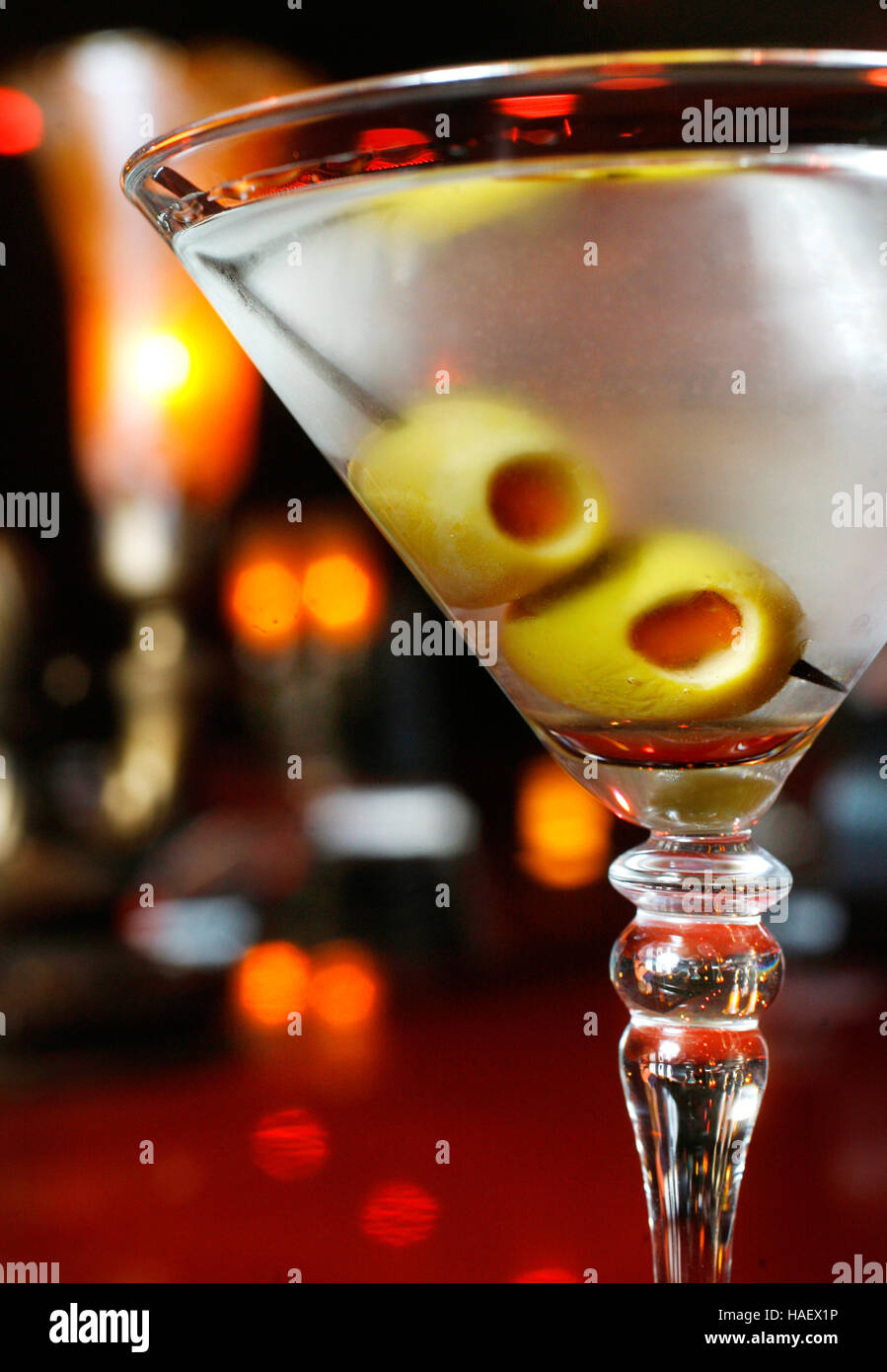 A martini with olives sits on a bar in a cocktail lounge. Stock Photo