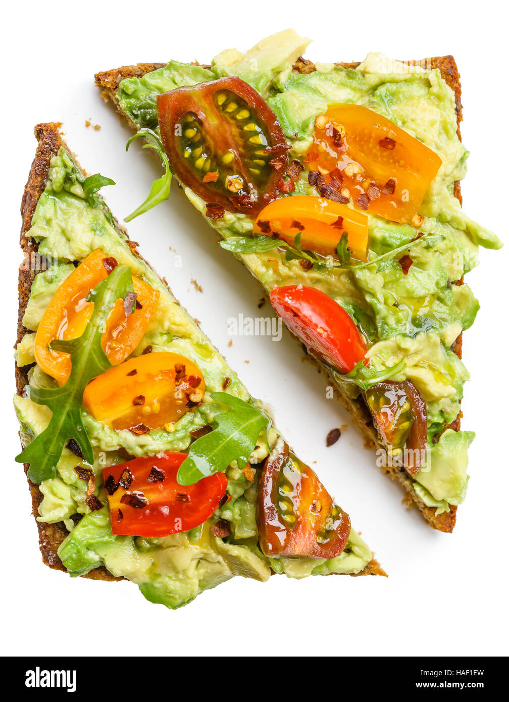 Slice of rye bread with avocado, colorful tomatoes and aragula leaves - Stock Image