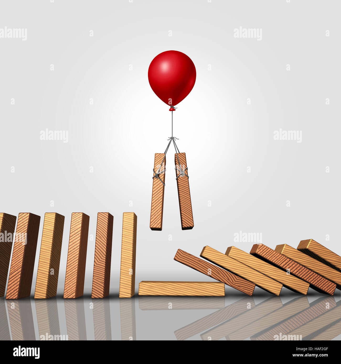 Downsizing business strategy as a balloon lifting up a pair of domino pieces allowing the gap to stop the falling - Stock Image