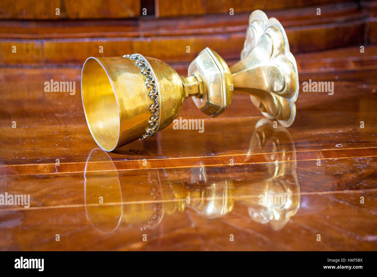 Golden grail turned on wooden background surface - Stock Image