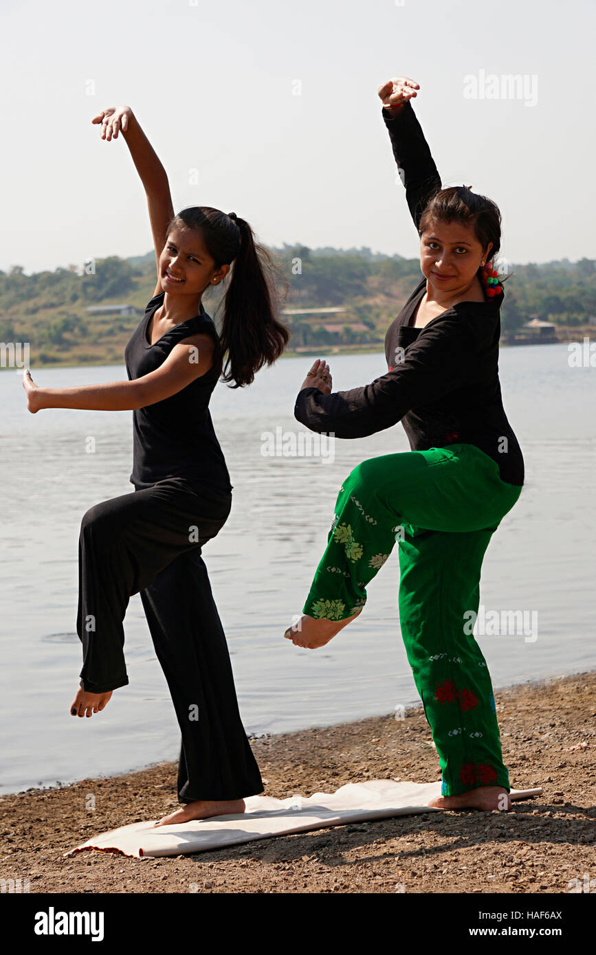 Girl and woman in starting position of side whirling movement called Kati-Paak, Pune, Maharashtra. - Stock Image