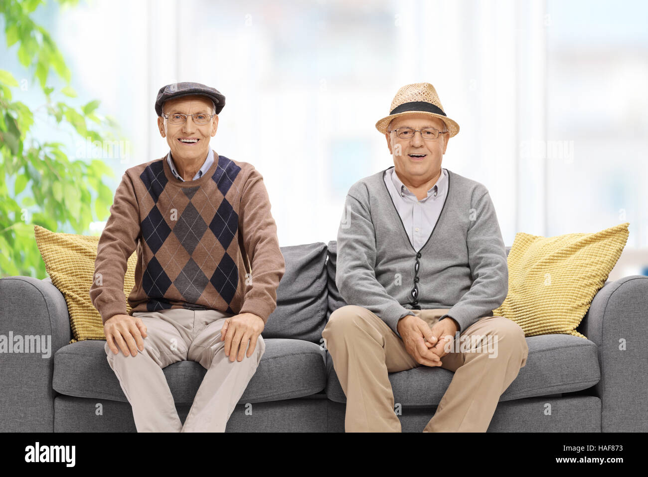Seniors sitting on a sofa and looking at the camera - Stock Image
